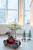 Arrangement of cloth mouse in red toy car and miniature fir tree