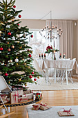 Gifts under Christmas tree in beige dining room
