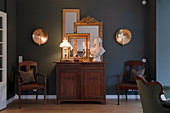 Gilt-framed mirror and bust on antique cabinet against dark wall