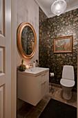 Elegantes Toilettenbad mit floraler Tapete und Goldrahmenspiegel