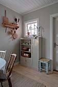 Alter Schrank vor grauer Wand in schlichter Wohnküche