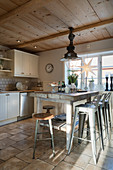 Rustic wooden table and metal stools in country-house kitchen