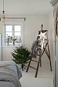 Small Christmas tree next to old stepladder decorated with fur blanket and paper star