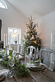 Festlich gedeckter Holztisch in Weiß, Grün und Grau zu Weihnachten