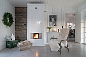 Armchair with sheepskin blanket in front of tiled stove in rustic living room