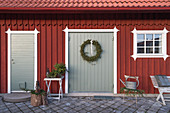 Christmas decorations outside Falu-red, Swedish house with paved courtyard