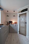 Old wooden pantry door in Scandinavian country-house kitchen
