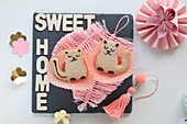 Cat-shaped biscuits on pink feathers made from string