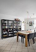 Black upholstered chairs at wooden table next to glass-fronted cabinets in dining room