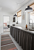 Black-and-white striped curtains below kitchen counter
