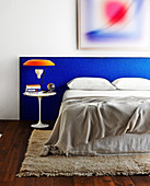 Double bed with headboard upholstered in blue fabric