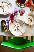 Gedeckter Tisch mit Tellern aus Scherben und goldenem Besteck