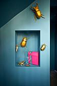 Goldene Deko-Käfer an blauer Wand mit Nische und pinkem Geschenk