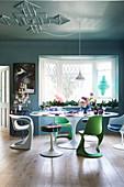 Bunt gedeckter Tisch mit Designerstühlen vorm Erkerfenster