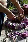 Hands tying wreath of ornamental cabbage leaves and sedums