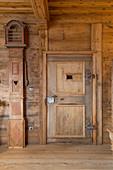 Antique longcase clock next to panelled door in rustic farmhouse parlour
