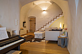 Piano in rustic living room with vaulted ceiling and staircase