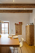 Modern wooden table in rustic parlour with old wooden ceiling beams