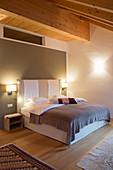 Bed against grey wall in bedroom with wooden ceiling beams
