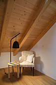 Armchair, standard lamp and side table below wood-clad sloping ceiling
