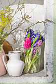 Vases of mimosa, hyacinths and hazel branches in niche in green wall
