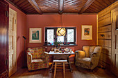 Armchairs at set table in front of red wall in rustic dining room