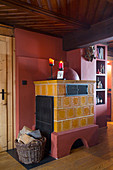 Yellow tiled stove against red wall in rustic living room