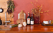 Chopping boards, wine and dried flowers in wooden vase