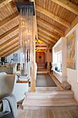 Rustic living room under sloping, wood-clad ceiling
