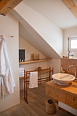 Wooden washstand in modern, country-house-style bathroom with sloping ceiling