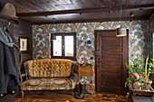 Rustic foyer with dark wooden ceiling and vintage-style wallpaper