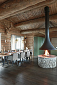 Open fire and country-house kitchen in rustic dining room