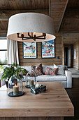 Round lampshade above coffee table in living room of log cabin