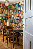 View of antique pedestal table in library seen through open panelled door