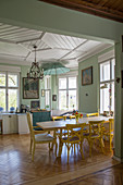 Yellow chairs around dining table in open-plan kitchen with panelled ceiling