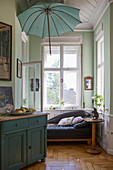 Parasol above sofa in window bay with mint-green walls in period building