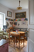 Round wooden table and wainscoting with picture ledge in cosy dining room