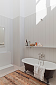 Free-standing bathtub against pale wooden cladding in bathroom