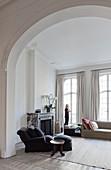 Blick durch Rundbogenöffnung auf Sessel und Kamin im Wohnzimmer