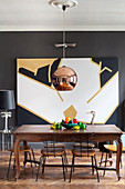Antique dining table and chairs below copper pendant lamp and modern artwork on wall
