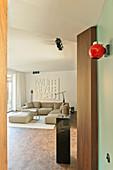 Helles Polstergarnitur im Wohnzimmer, rote Wandleuchte im Vordergrund