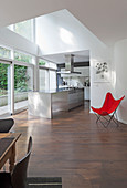 Classic, red Butterfly Chair in open-plan kitchen with island counter