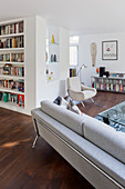 Bookcase and lounge area in open-plan interior