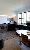 Oval dining table in large kitchen-dining room with black kitchen cabinets