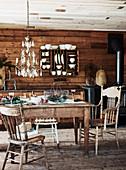 Rustikaler Esstisch vor Bretterwand mit Tellerboard