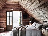 Doppelbett auf rustikalem Dachboden mit offener Balkontür