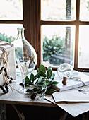 Anitke Weinflasche, Weinglas und Glaskugel auf Fensterbank