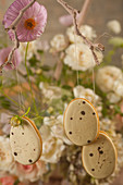 Biscuits iced to look like quails' eggs hanging from branch