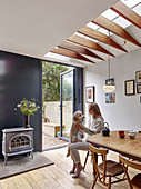 Woman and dog at dining table below skylight and next to door leading into garden