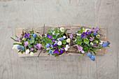 Spring flower arrangement decorated with birch bark on wooden board